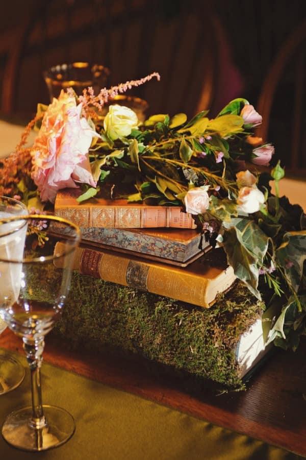 Bonitos libros cubiertos de musgo como centros de mesa min