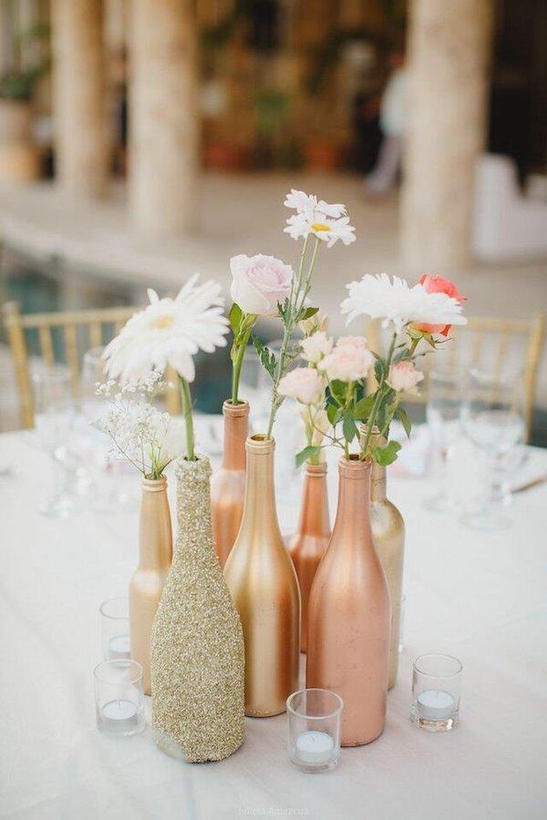 Centro de mesa de bricolaje con botellas de oro y cobre.